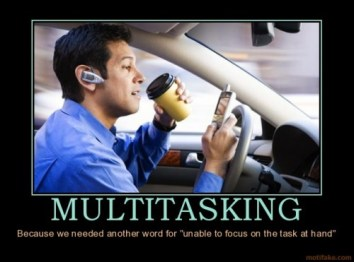 Picture of man driving while drinking coffee and texting on his mobile phone. Caption reads: Multitasking - because we needed another word for